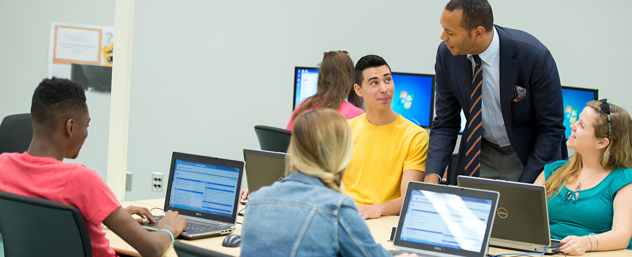 Penn State students interact with their instructor while working on laptops in a classroom.
