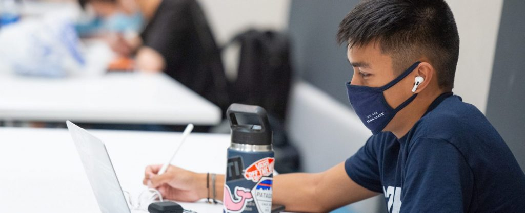 Student wearing a mask and holding a pen next to a computer
