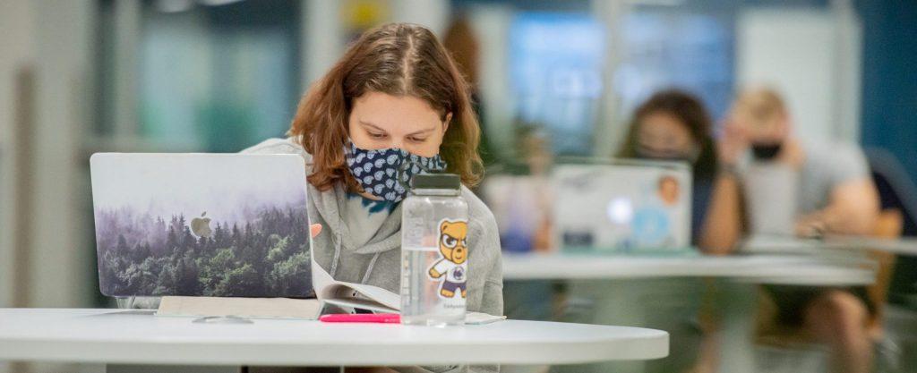 Student wearing mast at laptop